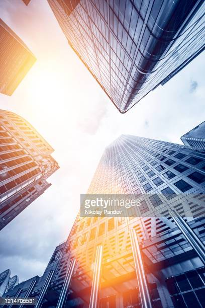 looking directly up at the skyline of the financial district in canary wharf, london, united kingdom - creative stock image - skyscraper stock pictures, royalty-free photos & images