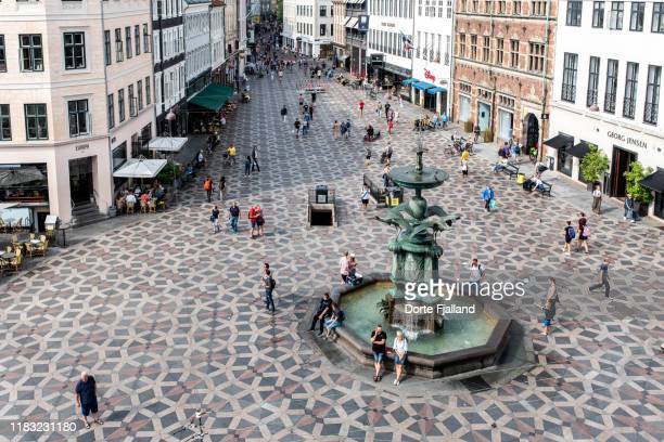 looking down at a fountain surrounded by a patterned pavement, people walking and buildings in the background - dorte fjalland stock pictures, royalty-free photos & images