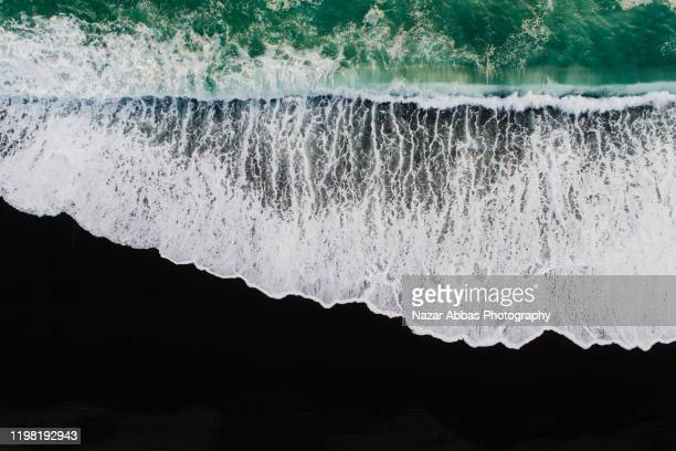 looking down at black sand beach. - sustainable development goals stock pictures, royalty-free photos & images