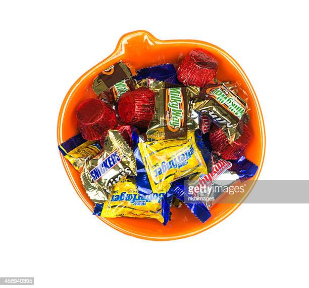 looking down at candy in pumpkin shaped bowl - bowl of candy stock photos and pictures