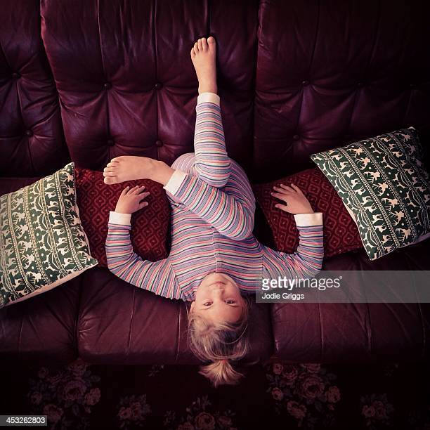 Looking down at child sitting upside down on couch