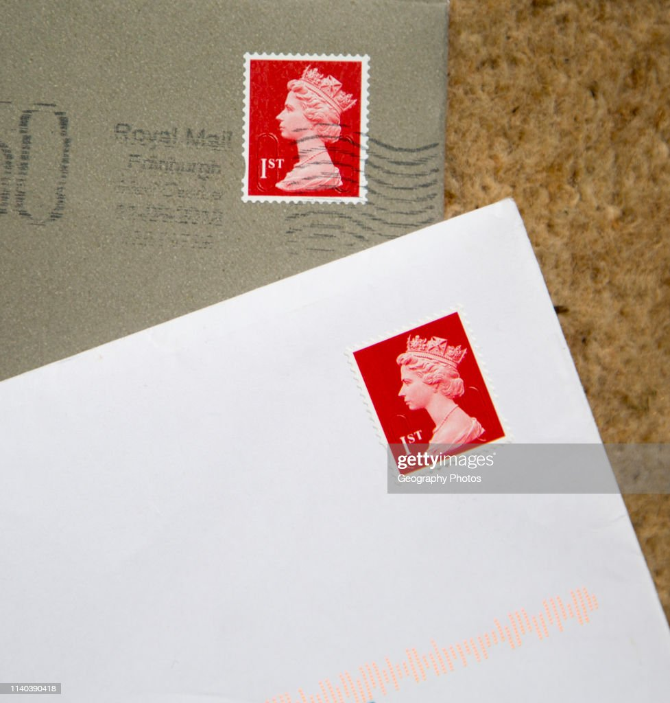 Looking down at letters in envelopes with red First class postage