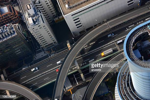 looking down at tokyo, japan highways and buildings - overhead view of traffic on city street tokyo japan stock photos and pictures