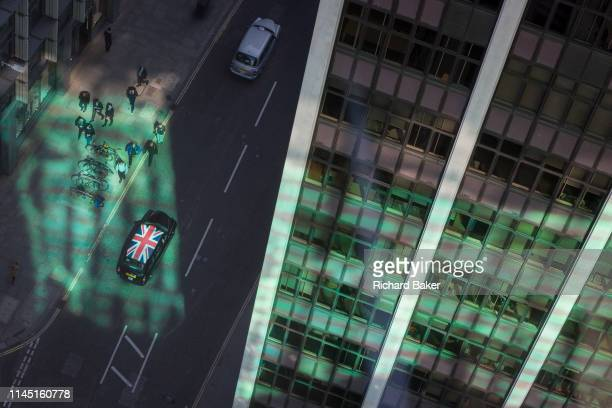 Looking down from an aerial view towards green reflected light and a passing taxi cab with a union Jack flag on its roof with passing business...