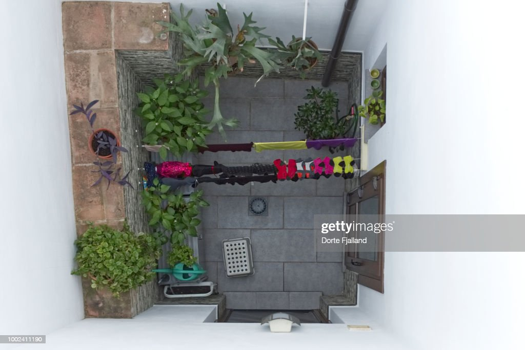 Looking down into a tiny patio with green plants and laundry : Foto de stock