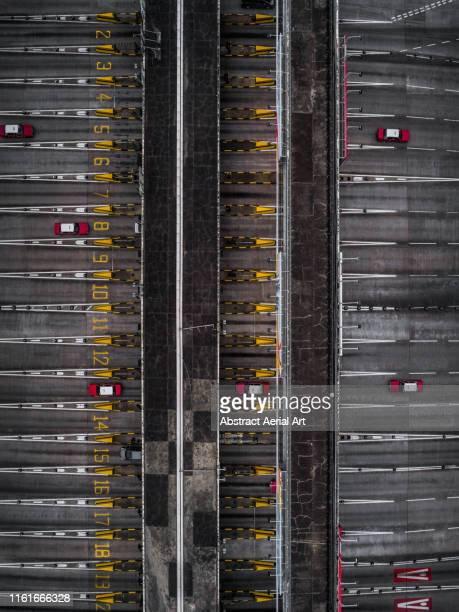 Looking down on a toll booth with red taxis on the highway, Hong Kong