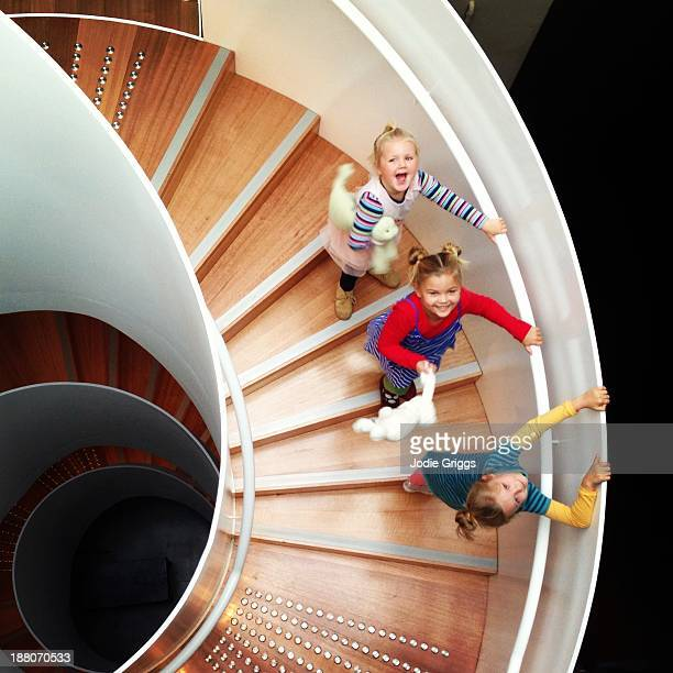 Looking down on children climbing spiral staircase