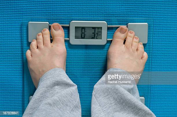 Looking down on woman's feet as she weighs herself