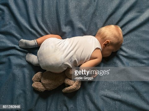 Looking down on young child sleeping uncovered on a bed