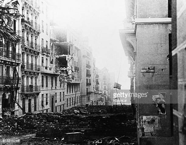 Looking down the Martin de los Heroes Street in Madrid during the Spanish Civil War with brick barricades across the street and the upper stories of...