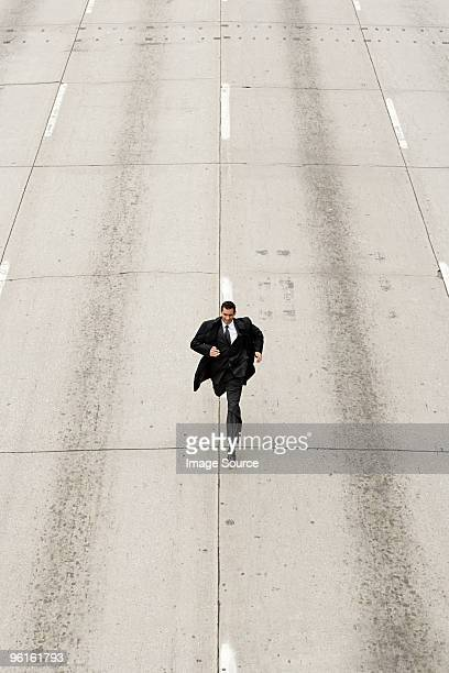 Looking down to a businessman running down a road