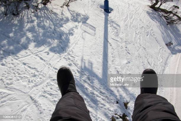 POV looking down to snowy ground from chairlift