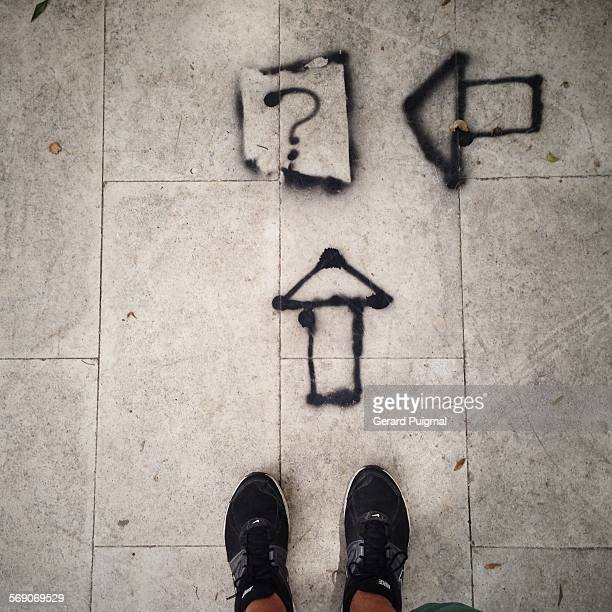 Looking down to the feet there is an interrogation symbol painted on the floor Picture taken in Aveiro in June 2015