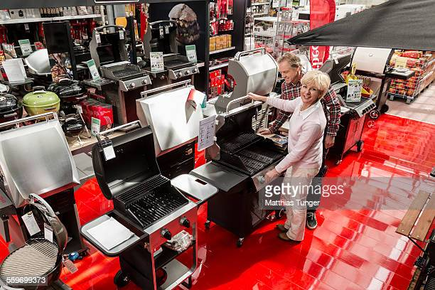 looking for a new barbecue in a hardware store - build grill stock photos and pictures