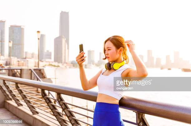 Looking mobile phone after jogging in city