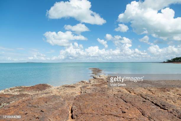 looking out across rocks at the clear blue ocean with clouds and blue sky - アーネム ストックフォトと画像