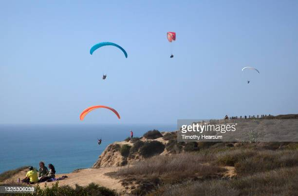 looking out at four paragliders; cliff and distant spectators in foreground; ocean and blue sky beyond - timothy hearsum fotografías e imágenes de stock