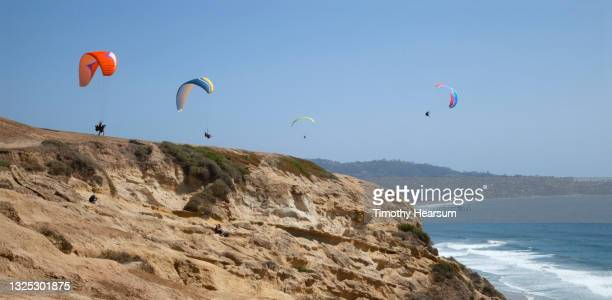 looking out at four paragliders; launching cliff in foreground; ocean, coastline and blue sky beyond - timothy hearsum imagens e fotografias de stock