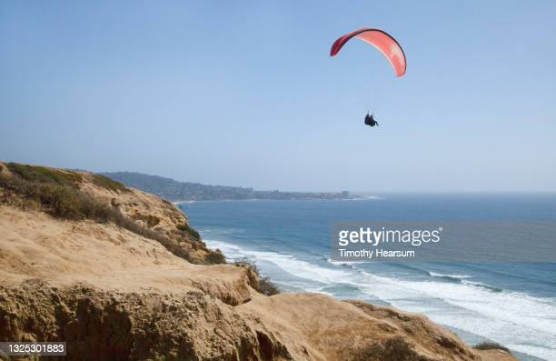 looking out at one paraglider; cliff in foreground; ocean, coastline and blue sky beyond - timothy hearsum fotografías e imágenes de stock