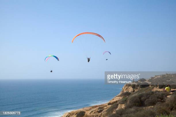 looking out at three paragliders; cliff and distant spectators in foreground; ocean and blue sky beyond - timothy hearsum ストックフォトと画像
