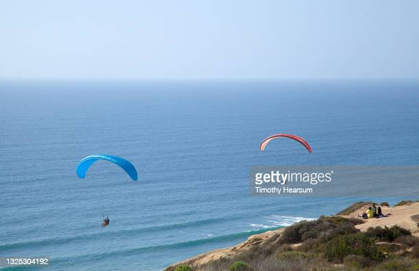 looking out at two paragliders; cliff and distant spectators in foreground; ocean and blue sky beyond - timothy hearsum fotografías e imágenes de stock