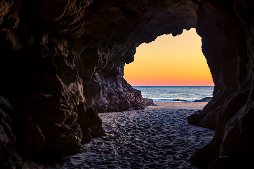 Looking out of a beach cave at sunset, Leo Carillo State Beach, California 916277500