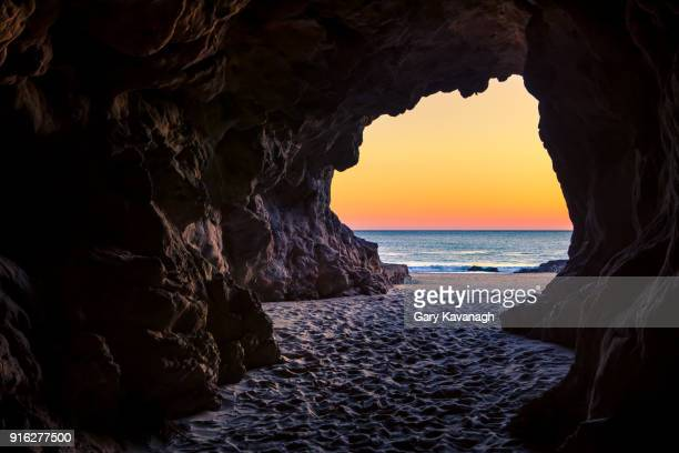 looking out of a beach cave at sunset, leo carillo state beach, california - cave stock pictures, royalty-free photos & images
