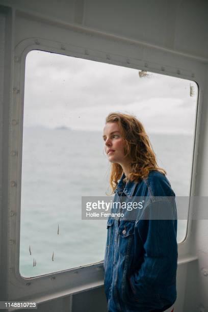 looking out of a ferry window 2 - handen in de zakken stockfoto's en -beelden