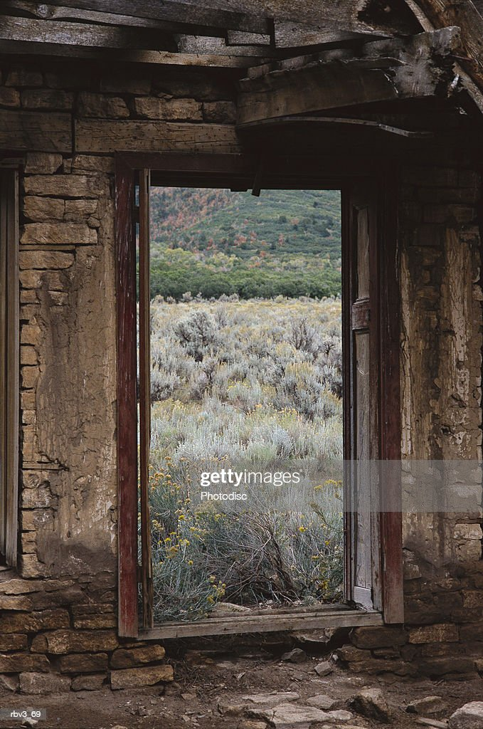 looking out of an abandoned adobe cabin to see sage brush and dead grass : Foto de stock