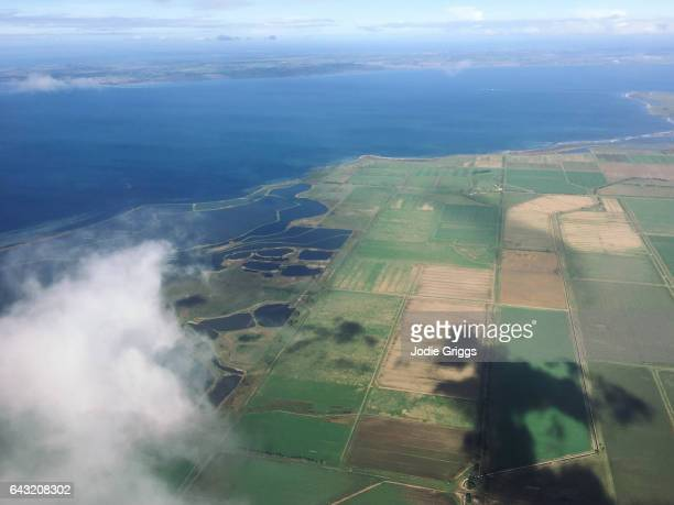 Looking out of an aircraft window at the fields and ocean below