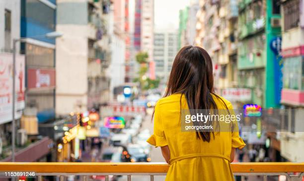 looking out over a hong kong street - yellow dress stock pictures, royalty-free photos & images