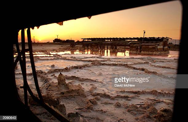 Looking out the window of a flooded trailer the sun sets behind a scene of briny mud and ruined homes at Bombay Beach on the west shore of the Salton...