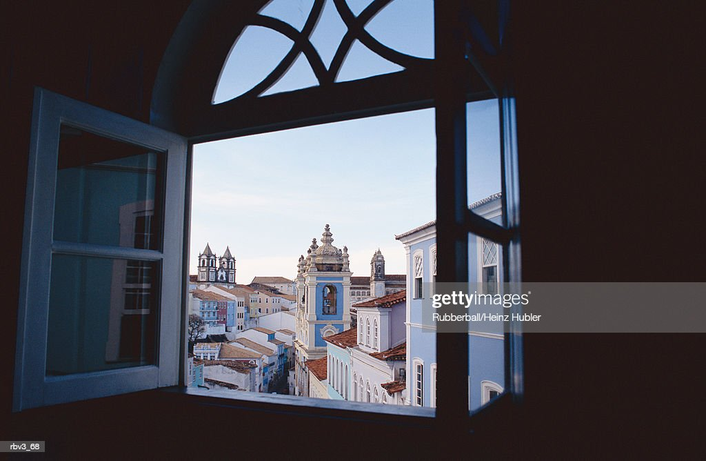 looking out the windows of a dark room to see buildings and the blue sky with white clouds : Stockfoto