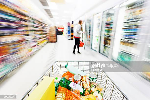 Looking over full shopping cart down motion-blurred supermarket aisle
