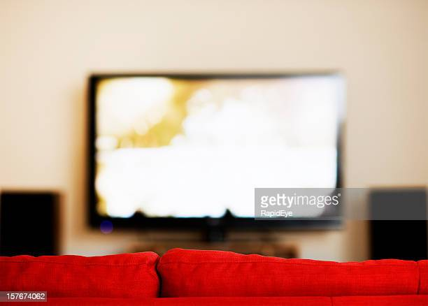 Looking over the back of a red sofa at television