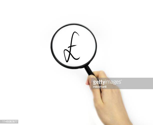 looking though a magnifying glass at currency sign - rescue stock pictures, royalty-free photos & images