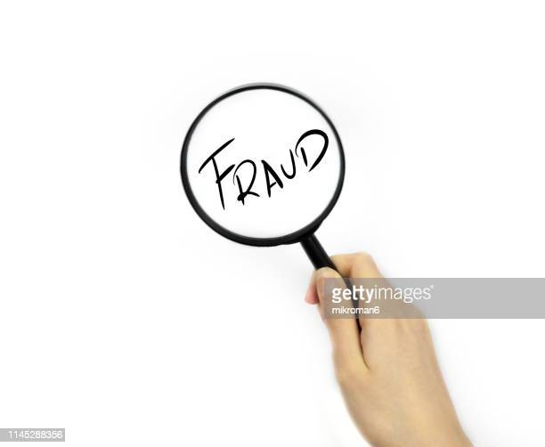 looking though a magnifying glass onto fraud - tax fraud stock-fotos und bilder