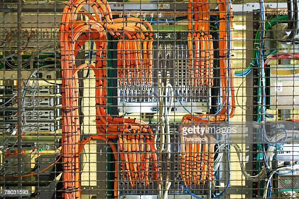 Looking through a cage to see orange cables going to the back of a rack of computer servers