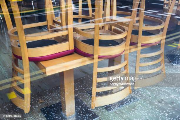 looking through a closed bar window from the street to chairs upside down on a table - sluiten stockfoto's en -beelden
