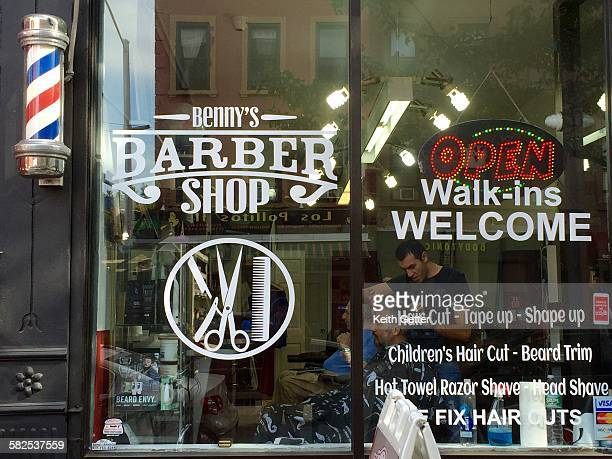 Looking through a glass facade window of a barber shop that also has a barbers pole on the exterior promoting the barber's craft Park Slope Brooklyn...