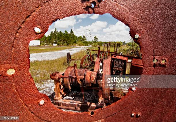 looking through a hole in a rusty discard at more abandoned, rust covered equipment. - rust colored - fotografias e filmes do acervo