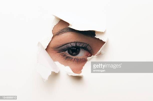 Schaut durch ein Loch im Papier