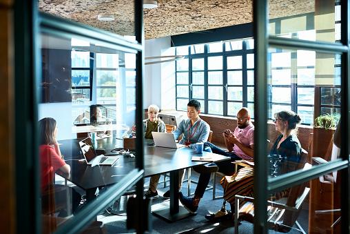 Looking through board room door at business strategy meeting - gettyimageskorea