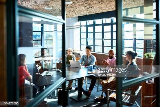 looking through board room door at business strategy meeting - creative occupation stock pictures, royalty-free photos & images
