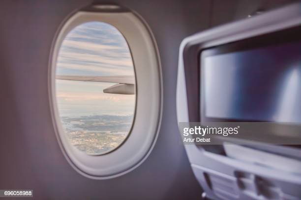 Looking through passenger window flying with new long distance airplane with nice nature views during travel vacations.