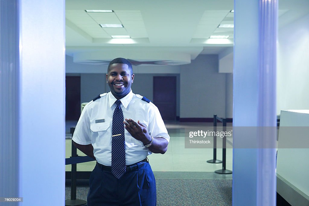 Looking through the metal detector to an airport security officer signaling a traveler to step forward : Stock Photo
