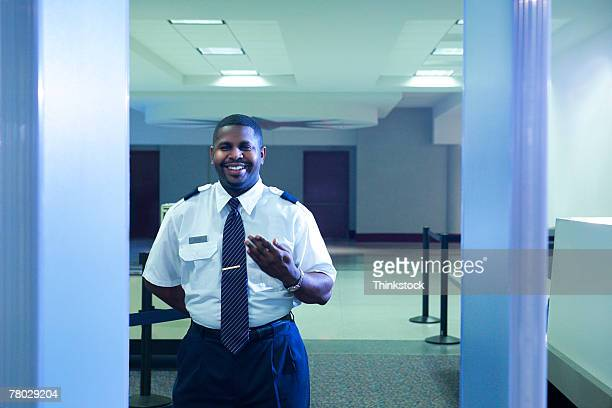 looking through the metal detector to an airport security officer signaling a traveler to step forward - security scanner stock pictures, royalty-free photos & images