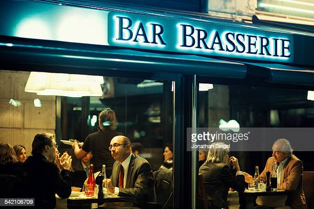 Looking through the window of a French brasserie in Bordeaux as diners chat and enjoy their dinner.