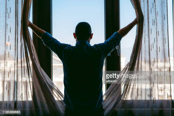 looking through the window - curtain stock pictures, royalty-free photos & images