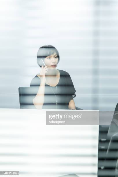 Looking Through Window Blinds at Woman on Telephone